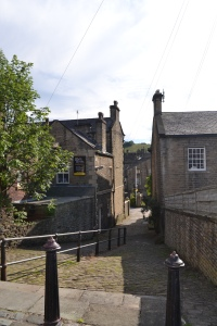 Alleyway down from the main road with the fictional pub entrance on the left