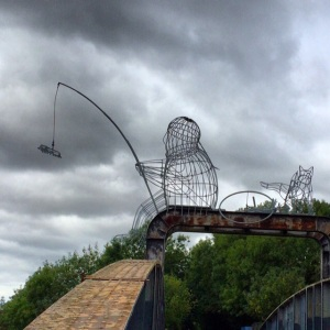 The Fisher of Dreams (man or woman) with bike and dog, sitting on Naburn Bridge along the cycle trail